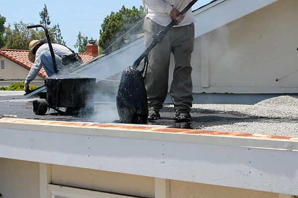 Workers installing tar, gravel, and asphalt on a flat roof