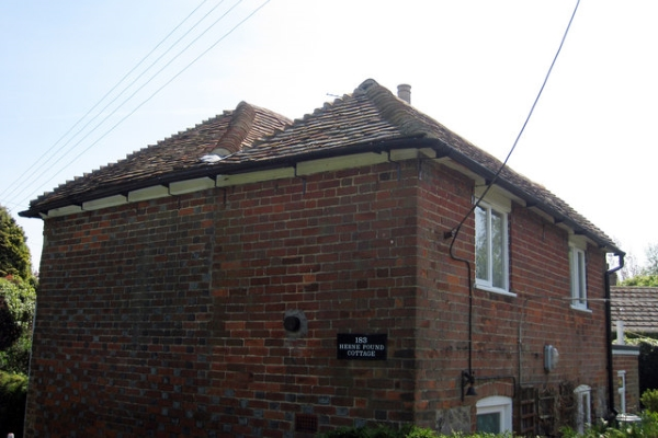 A simple hip-roofed cottage with brick sidings