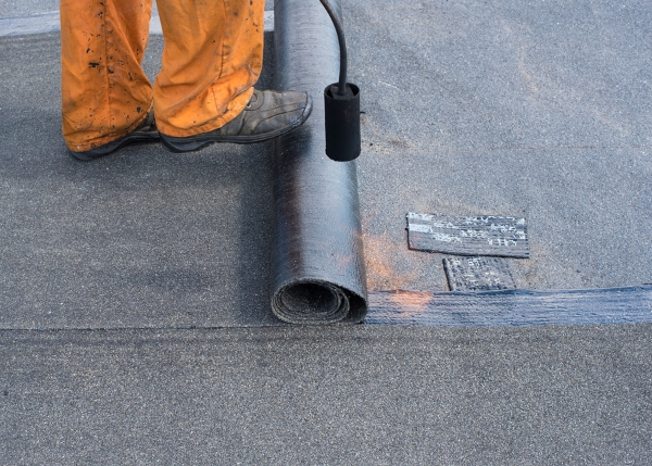contractor stepping on modified bitumen sheet
