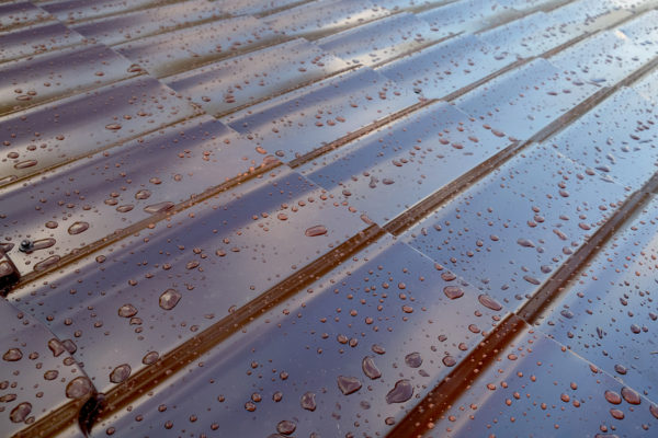 a brown metal roof with rain droplets