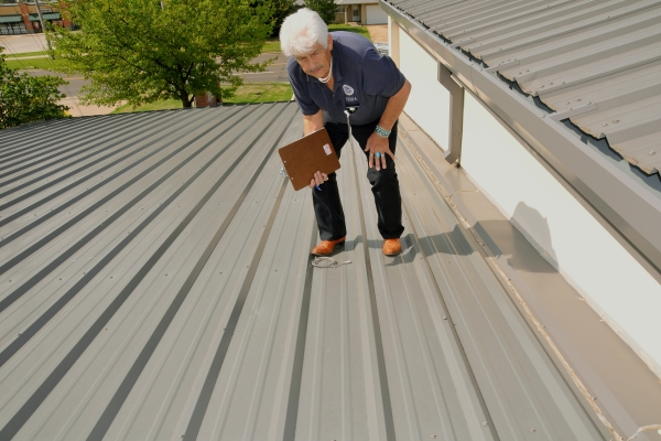 roofing contractor inspecting a metal roof for possible damages