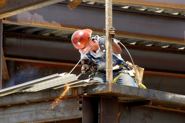 roofer welding a commercial metal roof
